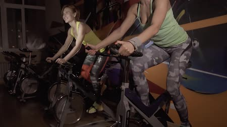 gymnasium : Two active sporty women enjoying their working out on stationary bicycles together Stock Footage