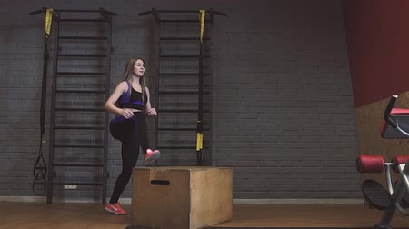 Female athletes doing box jumps at gym Stock Footage