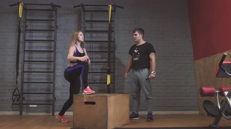 encouraging : Attractive sports people are doing box jumps while working out in gym