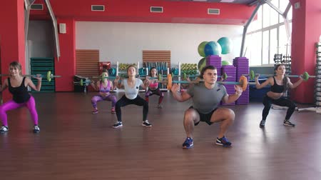 perte de poids : Group of strong male and female adults holding barbells in ftness exercise studio