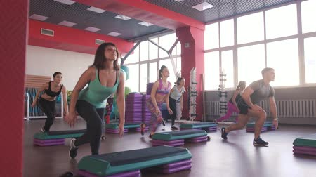 leisureactivity : Step group training, smiling people doing exercise Stock Footage