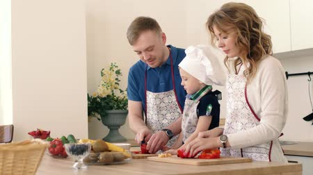 picado : A beautiful family is preparing a delicious fruit salad in the kitchen of the house. Stock Footage