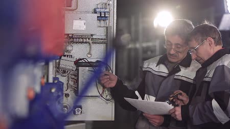 labor union : Two factory electricians discussing electric meter. Stock Footage