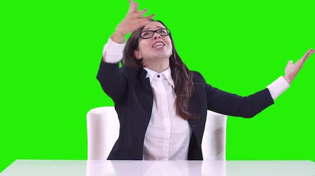 koperta : Portrait of a woman in the office on a green background. The brunette in glasses rejoices, smiles and dances at work