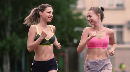 fitness tracker : Two running women Fitness athletic friends women jogging in the urban city
