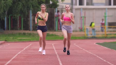 бегун трусцой : Two athletes compete in the race at the stadium in the morning, in the summer, on the street Стоковые видеозаписи