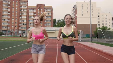 ジョガー : Portrait of two young athletes who compete in the race at the stadium in the morning, summer, outdoors 動画素材