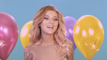 bachelorette party : Beautiful young woman in a golden dress at a party. She is smiling and having fun on a blue background among the balloons. In her hands is a sparkler.