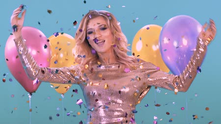 cerceta : woman dancing at a party in a beautiful shiny dress. With balloons and confitti