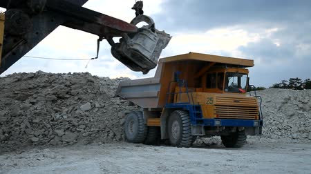 maquinaria : Heavy mining dump truck being loaded with iron ore