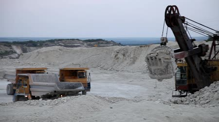 экскаватор : Heavy mining dump truck being loaded with iron ore