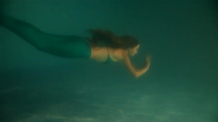 iluminado para trás : Beautiful woman mermaid diving and swimming underwater Stock Footage