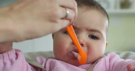 infante : Little girl is feeding her by mom Stock Footage