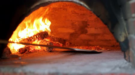 wood : Chef loading pizza into hot oven. HD 1080i. Stock Footage