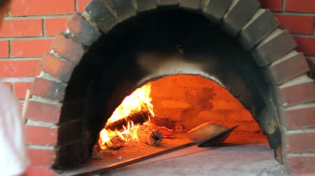 prepare food : Bun being baked in a wood fire brick oven in a restaurant
