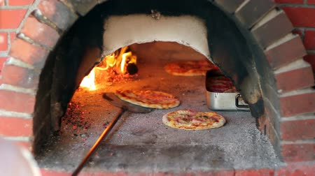 ресторан : Pizza being baked in a wood fire brick oven in a restaurant. HD 1080i. Стоковые видеозаписи