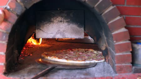 cegła : Large pizza being baked in a wood fire brick oven in a restaurant. HD 1080i.