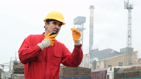 sipariş : Factory worker in red overalls wearing hardhat and communicating over walkie-talkie. HD 1080i.