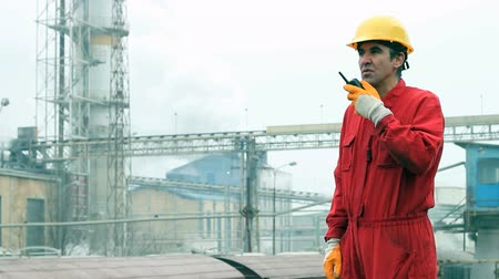 portre : Factory worker in red overalls wearing hardhat and communicating over walkie-talkie. HD 1080i.  Stok Video
