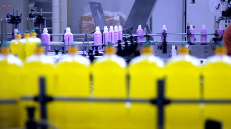 cleaning products : A conveyor belt carries filled bottles of liquid dishwashing detergent.