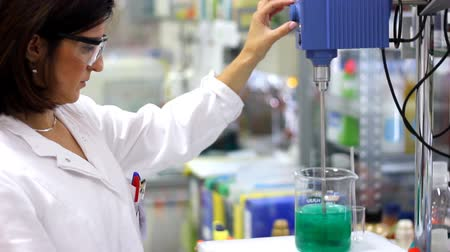 ученый : Chemist woman workw with lab mixer and mixing chemicals in an experiment. Стоковые видеозаписи