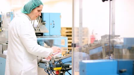 gyógyszertár : A female technician is monitoring the process of pill packaging. HD 1080i.
