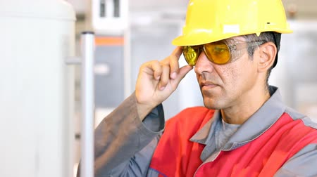 védősisak : Portrait of a worker wearing protective helmet and safety glasses.