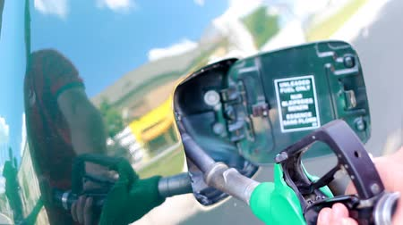 ekonomi : Gas station worker using a fuel nozzle. HD 1080i. Canon EOS 550D