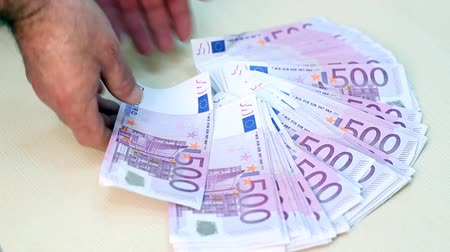 sucessful : Banker throws bundle of 500 euro banknotes on the table. HD 1080p.