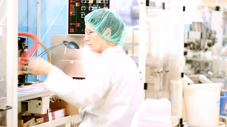 robótico : Robotic arm lifting ampoules at packaging line in pharmaceutical factory. HD 1080p.