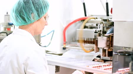 pharmaceuticals : Pharmaceutical worker at work beside ampule packaging line.
