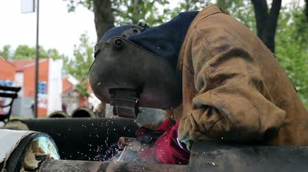 biztonság : Welder with protective equipment welding outdoors. 1080p.
