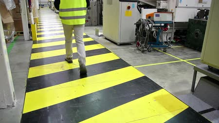 biztonság : Industrial safety. Manager walking across yellow-black safety area inside the factory.