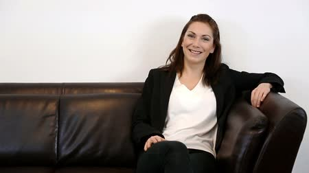 bizneswoman : A young and attractive businesswoman sitting down in a sofa wearing a black suit and white shirt, feeling great! White background.