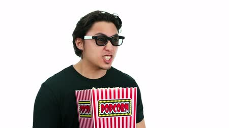pipoca : A young and attractive man sitting down at the cinema watching a 3D movie holding a large popcorn bowl. White background.