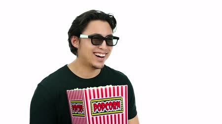řvát : A young and attractive man sitting down at the cinema watching a 3D movie holding a large popcorn bowl. White background.