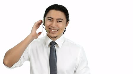 японский : Young and attractive businessman wearing a shirt and tie. Talking on a headset. White background. Стоковые видеозаписи
