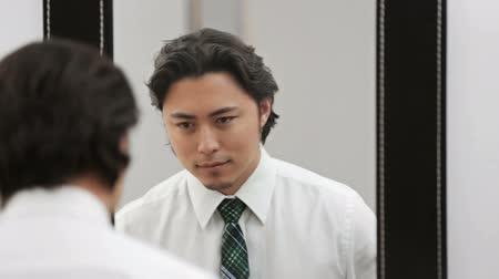iyi giyimli : An attractive man wearing a shirt and tie, tying his tie in front of a mirror. Feeling confident and successful.