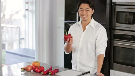 kesme tahtası : A young and good looking man in his 20s wearing a white shirt preparing a dinner in the kitchen with lots of vegetables. Freezer and refrigerator in the background. Big smile on his face.