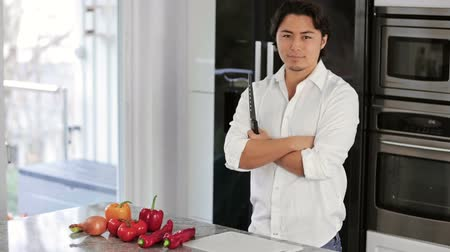 разделочная доска : A young and good looking man in his 20s wearing a white shirt preparing a dinner in the kitchen with lots of vegetables. Freezer and refrigerator in the background. Big smile on his face.