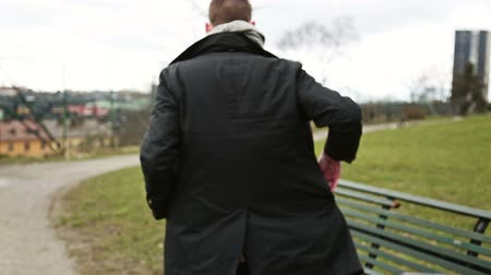 arkasında : A man walking wearing a black jacket and scarf, with view from behind. He sits down at a bench.
