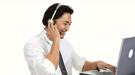 krawat : An attractive businessman wearing a white shirt and grey tie, with a headset. Talking on the phone while working on his computer. White background.