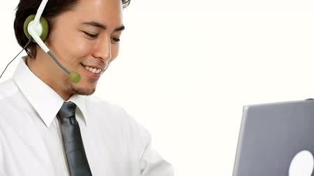 podnikatel : An attractive businessman wearing a white shirt and grey tie, with a headset. Talking on the phone while working on his computer. White background.