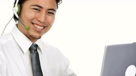 зубастая улыбка : An attractive businessman wearing a white shirt and grey tie, with a headset. Talking on the phone while working on his computer. White background.