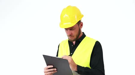 biztonság : Attractive construction foreman in his 20s, wearing a yellow safety helmet with a yellow vest, holding a clipboard. White background.