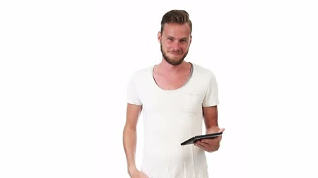 tshirt : A man wearing a tshirt standing against a white background, holding a digital tablet, working. Feeling satisfied.