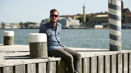 atracação : A 29 year old man sitting outside in a harbor by the water, wearing a jeans shirt and jeans with sunglasses. A sunny summer day. Stock Footage