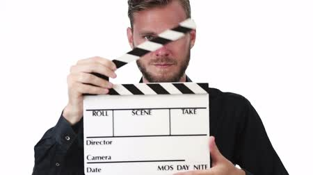 film slate : Attractive movie worker wearing a black shirt, holding a movie slate, clapping in front of camera. White background. Stock Footage