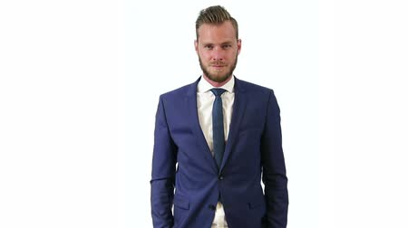 mavi arka : A handsome businessman wearing a blue suit, blue tie and white shirt. Standing against a white background. Stok Video