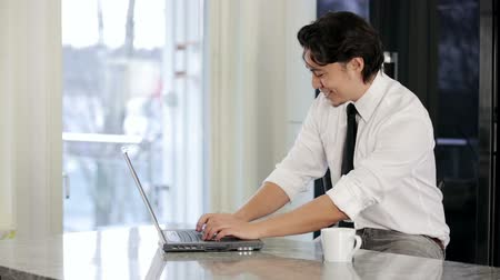 checagem : An attractive businessman wearing a shirt and tie, working from his home office and drinking from his coffee mug. Smiling looking at the computer screen. Vídeos